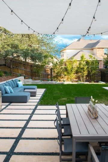 Backyard with a mix of hardscaping tiles and grass. A table with 8 chairs sits on the hardscaping covered with a white awning.